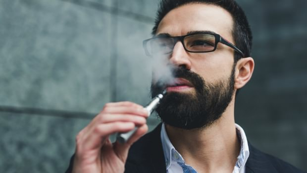 Businessman smoking E-Cigarette